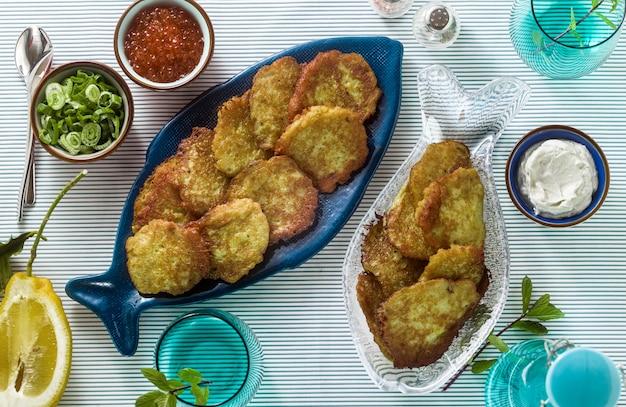 Tortini di pesce serviti sul tavolo con caviale rosso, cipolle verdi e panna acida. piatto di pesce fatto in casa