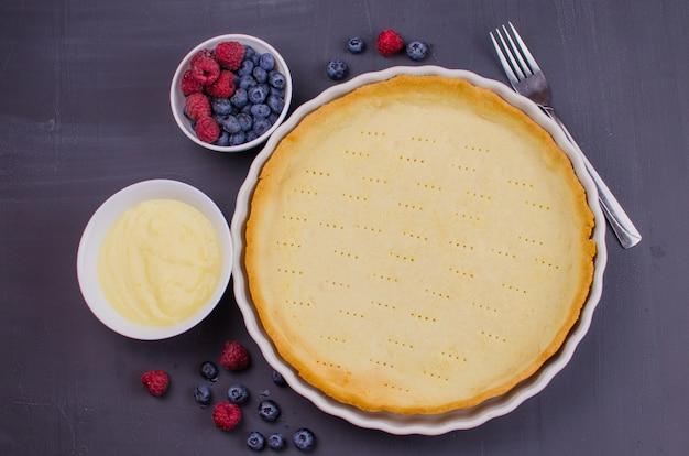 Tortino delizioso di mirtilli e lamponi con crema alla vaniglia