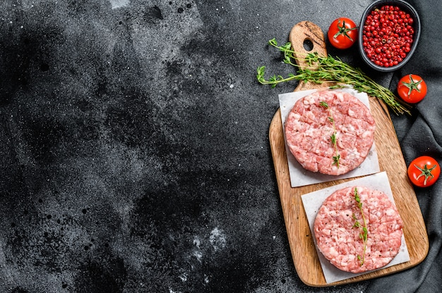 Tortino di pollo crudo, cotolette di carne macinata su un tagliere. trito biologico. vista dall'alto. copia spazio