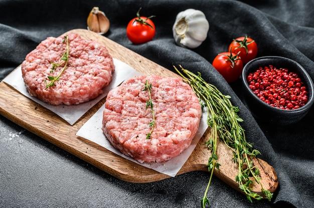 Tortino di pollo crudo, cotolette di carne macinata su un tagliere. trito biologico. vista dall'alto