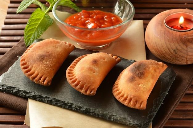Tortino di tonno fatto in casa con salsa di pomodoro sul tavolo di legno