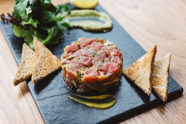 Tortino di tonno rosso piccante con salsa agrodolce e piccante. servito con pane tostato e insalata su lastra di pietra nera.