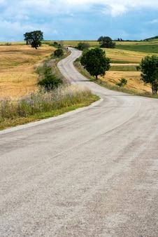 Tortuosa strada di campagna che porta a basse colline