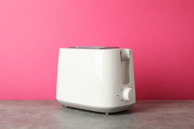 Tostapane sul tavolo grigio su sfondo rosa, spazio per il testo
