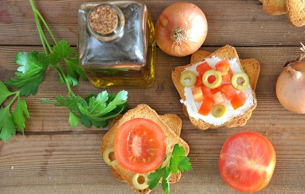 Tostare con pomodoro, olio, olive verdi sul tavolo di legno