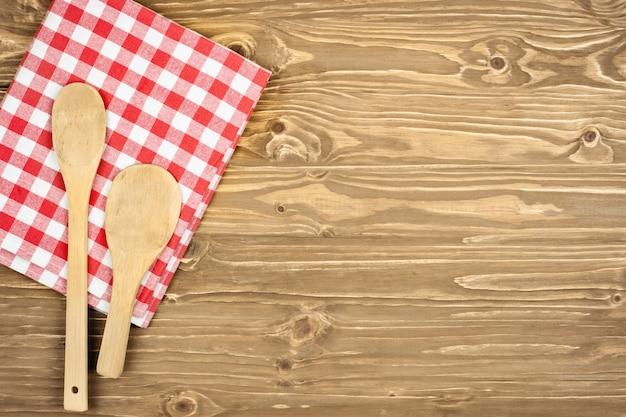 Tovaglia a quadretti rossa e cucchiaio di legno per cucinare e cuocere. sfondo con spazio di copia. orizzontale.