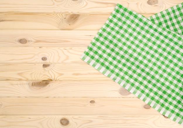 Tovaglia a quadretti verde sulla tavola di legno