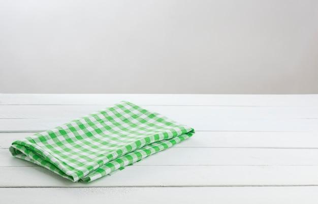 Tovaglia piegata verde sulla tavola bianca