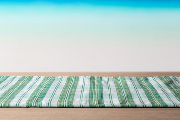 Tovaglia verde sulla tavola di legno davanti alla spiaggia tropicale