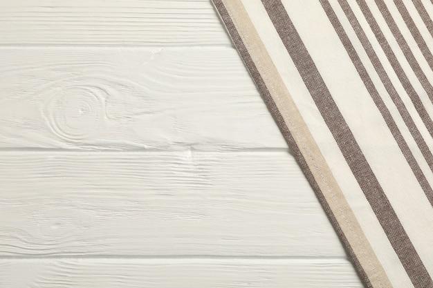 Tovaglioli del tessuto su fondo di legno bianco, spazio per testo