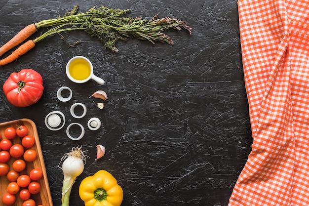 Tovagliolo a quadretti e ingredienti sul piano di lavoro della cucina