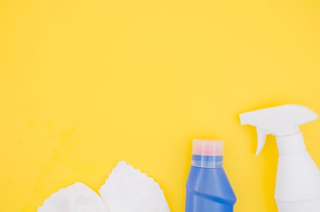 Tovagliolo bianco; flacone spray e detergente bottiglia blu con copia spazio per scrivere il testo su sfondo giallo