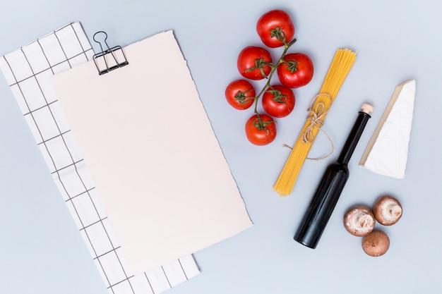Tovagliolo; carta bianca vuota e ingrediente per cucinare la pasta in superficie