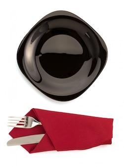 Tovagliolo con piatto, forchetta e coltello su bianco