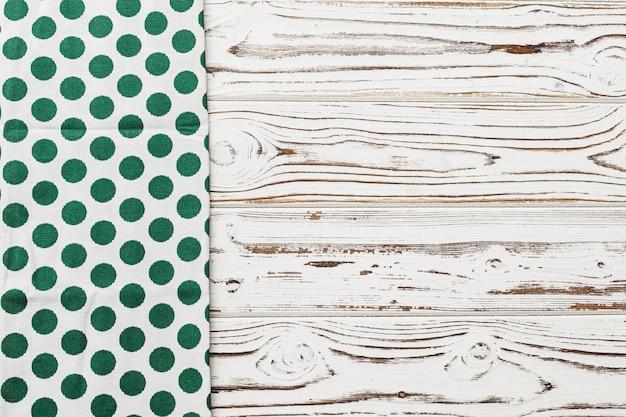 Tovagliolo verde a pois su fondo di legno stagionato, spazio della copia