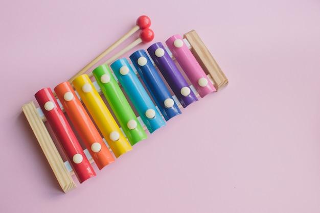 Toy xylophone di legno colorato arcobaleno su bacground rosa. giocattolo glockenspiel in metallo e legno