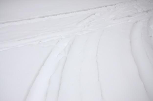 Tracce dalle ruote della macchina su una strada coperta di neve.
