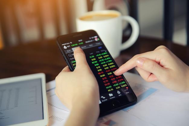 Trading online su smartphone con la mano donna bussiness