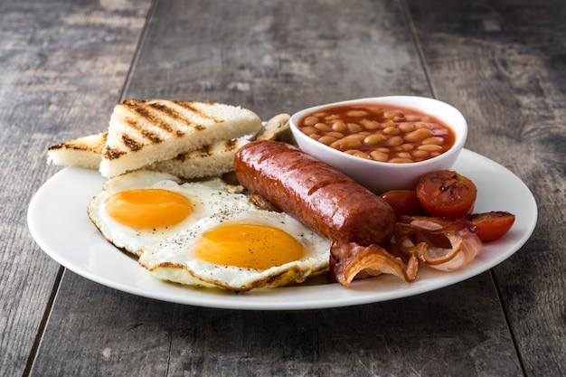 Tradizionale colazione inglese completa con uova fritte, salsicce, fagioli, funghi, pomodori grigliati e pancetta su superficie di legno