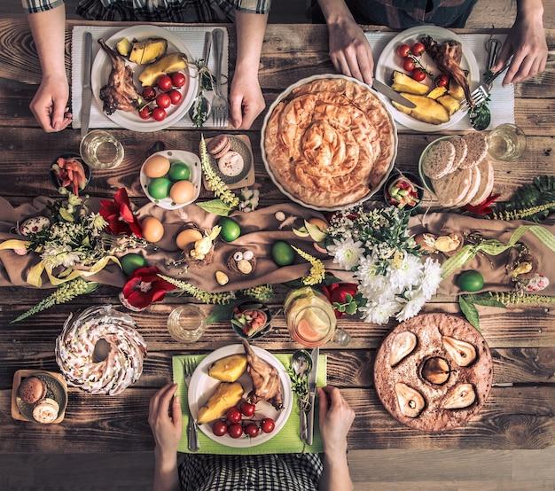 Tradizionale festa di pasqua, festa di vacanza di pasqua. amici in vacanza o famiglia al tavolo festivo con carne di coniglio, verdure, torte, uova, vista dall'alto. mani degli amici che mangiano e bevono insieme.