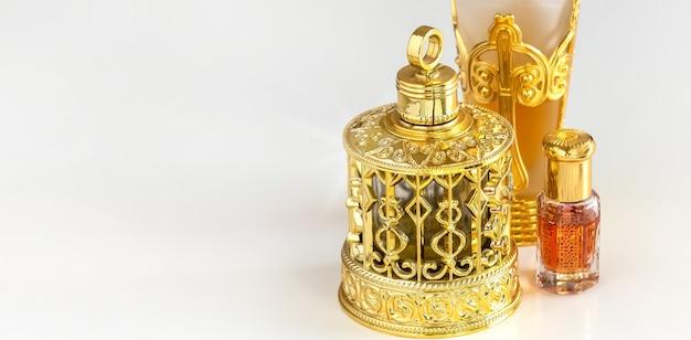 Tradizionale fiasco ornato d'oro di profumi di olio di oud arabi. sfondo bianco isolato copia spazio