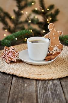 Tradizionale glassa di zucchero di pan di zenzero di natale a forma di omino divertente e una tazza di caffè espresso caldo