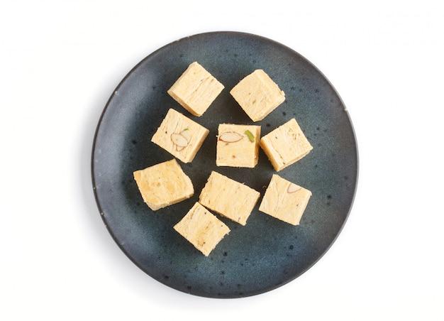 Tradizionale indiano caramelle soan papdi nel piatto di ceramica blu isolato su uno sfondo bianco