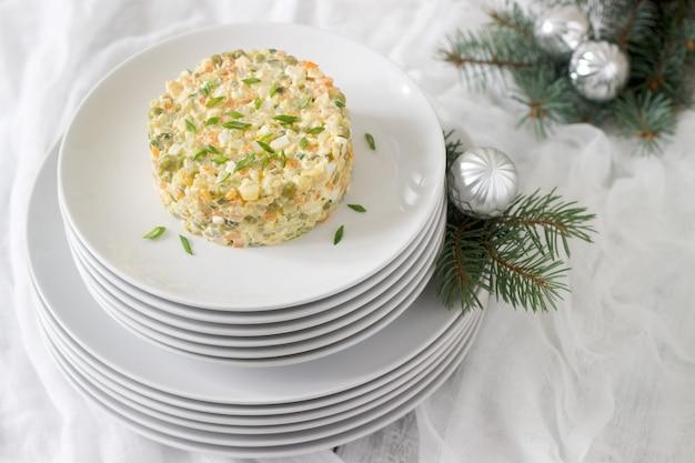 Tradizionale insalata celebrativa olivier su un piatto bianco con decorazioni di capodanno o natale. tradizioni sovietiche.