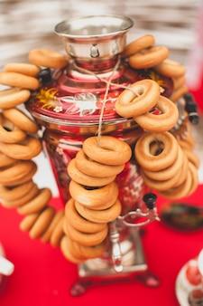 Tradizionale samovar dipinto in ottone russo su una tovaglia rossa, simbolo dell'ospitalità. panini croccanti, essiccazione o bagel sono appesi al samovar