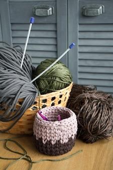 Tradizionali filati colorati per hobby a maglia in un cestino di paglia eco su una superficie di legno chiaro.