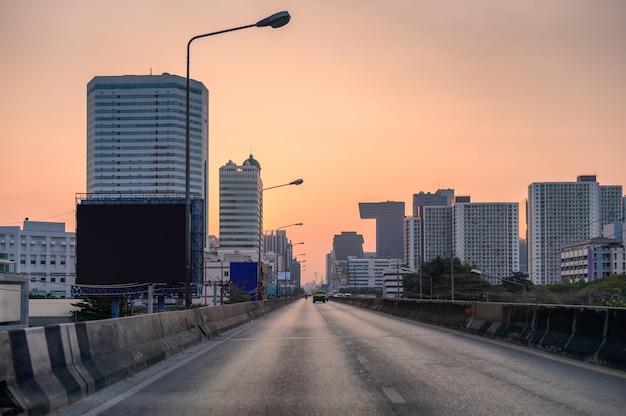 Traffico della strada principale con costruzione nella città al tramonto