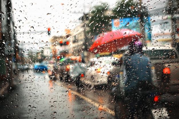 Traffico intenso nelle ore di punta sotto la pioggia, vista attraverso la finestra e composizione in profondità di campo.