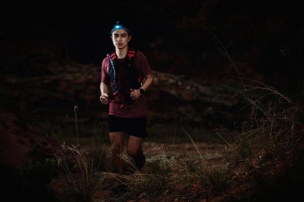 Trail runner in esecuzione sulla strada rocciosa nella notte