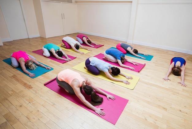 Trainer assistere gruppo di persone con bambino posa esercizio yoga