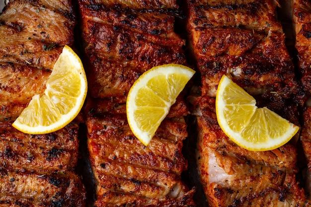 Trama alla griglia di pesce fresco. salmone alla griglia con una fetta di limone succoso