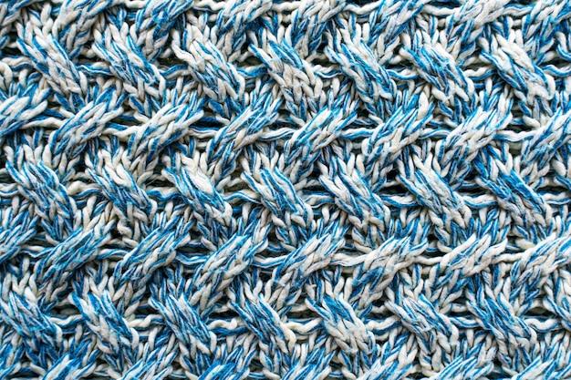Trama blu e bianca di un tessuto di lana lavorato a maglia con una trama fantasia. maglione sullo sfondo