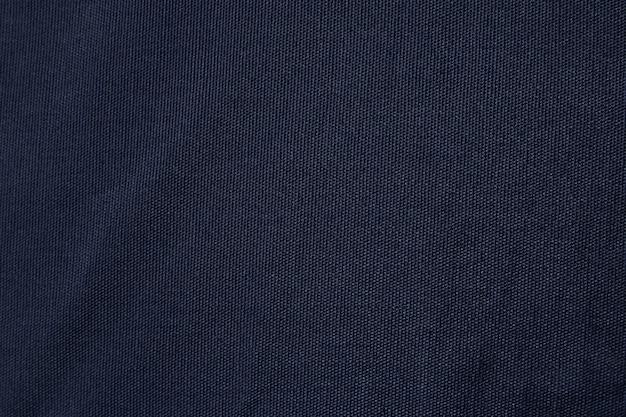 Trama del tessuto di tela blu scuro. fondo in bianco del modello della tessile del cotone.