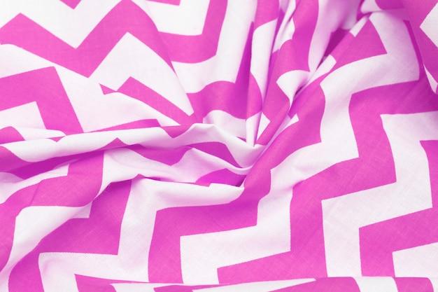 Trama del tessuto rosa e bianco spiegazzato con un motivo.