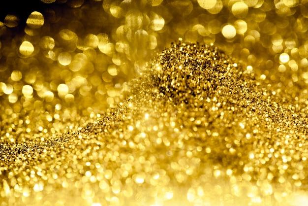 Trama di illuminazione bokeh scintillio dorato sfocato sullo sfondo astratto
