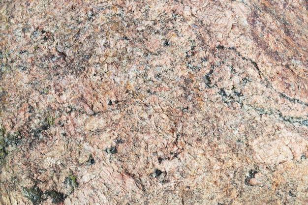 Trama di pietra naturale. superficie di granito beige o rosa con macchie nere.