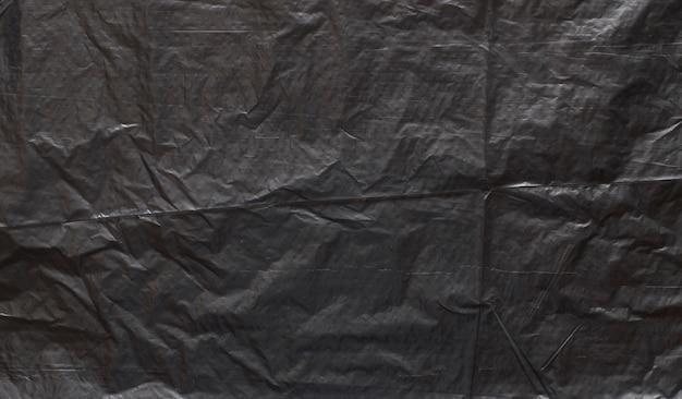 Trama di polietilene scuro con lividi e sfondo di polvere