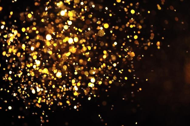 Trama di scintillio dorato colorfull offuscata sfondo astratto per la vigilia di natale capodanno o natale