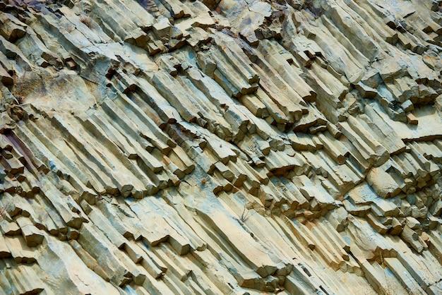 Trama di sfondo della lava vulcanica pietrificata sulla costa.