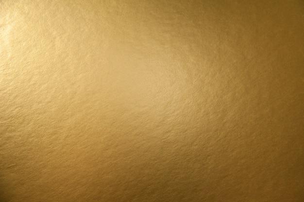 Trama di sfondo della superficie di carta metallica dorata per la progettazione di carte di natale o capodanno