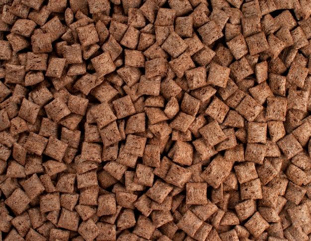 Trama di sfondo di cuscini di cioccolato. pastiglie di cereali al cioccolato marrone.