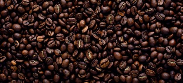 Trama di sfondo di un gran numero di chicchi di caffè tostato marrone fragranti e freschi. una delle fasi di produzione del caffè naturale