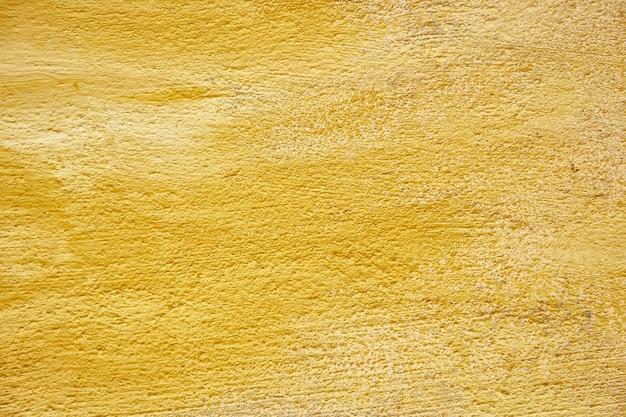 Trama di sfondo giallo. vecchia parete verniciata dura nello stile del grunge. vista da vicino