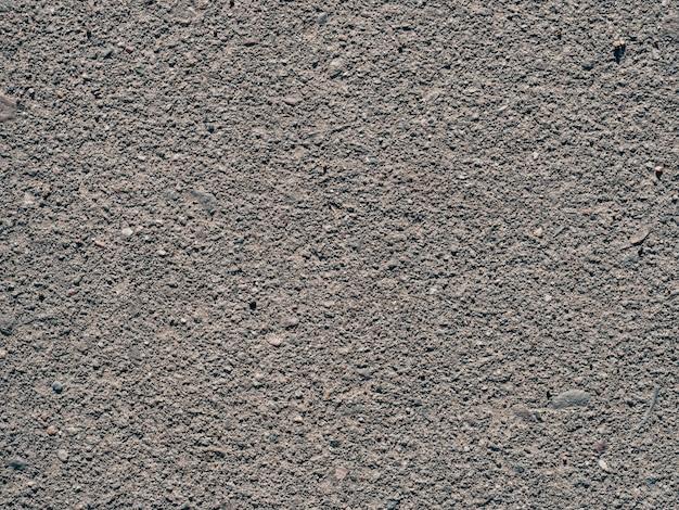 Trama di sporco vecchio asfalto con pietre close-up