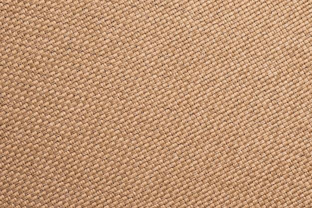 Trama di tela, sfondo marrone tessuto. superficie della tela di sacco, materiale di licenziamento, primo piano di carta da parati tessile insaccante