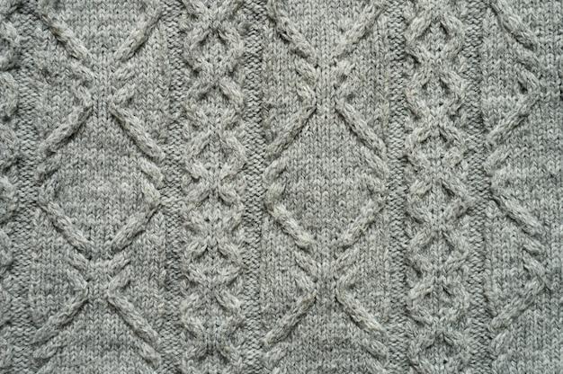 Trama di tessuto a maglia grigia senza cuciture con trecce. trama a maglia di maglione o sciarpa o plaid. sfondo grigio lavorato a maglia. primo piano, vista dall'alto.